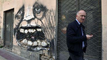 Au centre d'Athènes le 2 avril dernier : un passant dans une rue où s'accumulent les commerces abandonnés...