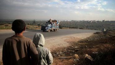 Des enfants regardent un camion de déplacés dans le village d'al-Mastumah, près de la ville d'Idleb, dans le nord-ouest de la Syrie, le 24 décembre 2019