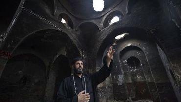 Un prêtre copte montre les dégâts causés dans une église par une attaque islamiste à Delga, dans le centre de l'Egypte, le 29 septembre 2013