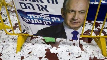 Des bulletins de vote autour d'une affiche de campagne du Premier ministre sortant et candidat du Likoud aux législatives israéliennes Benjamin Netanyahu, le 18 mars 2015 à Tel-Aviv