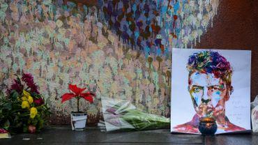 Hommage d'anonymes devant une fresque à Londres