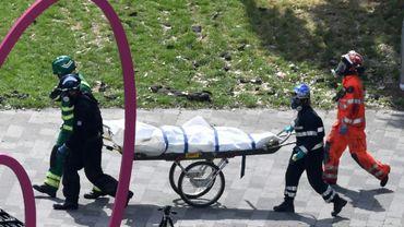 Des policers et des secouristes évacuent le corps d'une victime de l'incendie de la tour Grenfell à Londres, le 16 juin 2017