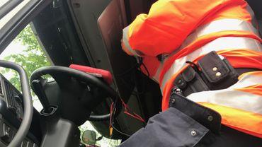 Un policier tente de trouver l'aimant qui modifie les données du tachygraphe