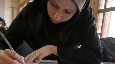 Une étudiante dessine à la main le motif d'un tapis persan