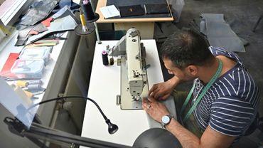 Penché sur sa machine à coudre, le Syrien Khaldoun Alhussain transforme un canot pneumatique en sac ou cabas, dans l'atelier de la petite entreprise mimycri à Berlin