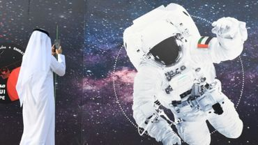 Un passant photographie l'image d'un astronaute dont le vêtement porte le drapeau émirati, devant le centre spatial Mohammed Bin Rashid à Dubaï, le 25 septembre 2019.