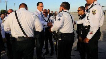 Mitt Romney, candidat à l'élection présidentielle, salue des policiers avant d'embarquer dans un avion, le 23 octobre 2012 à West palm Beach, en Floride