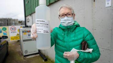Un client, portant un masque de protection, achète du désinfectant produit dans une distillerie de gin, à Tenure, en Irlande, le 18 mars 2020.
