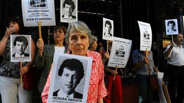 Beatriz Cantarini de Abriata, la mère de Hernan Abriata, tient un portrait de son fils disparu en 1976, aux côtés de proches brandissant des portraits de l'ex-policier argentin Mario Sandoval, le 9 avril 2014 à Buenos Aires