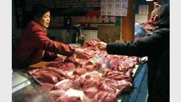 Une femme achète du porc dans un marché de Pékin le 30 janvier 2011