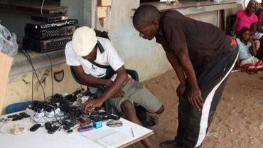 Un client fait recharger son téléphone portable, le 12 février 2013, dans la ville de Xai Xai, au sud du Mozambique