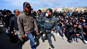 Un policier escorte des immigrés tunisiens qui vont être évacués de Lampedusa, le 29 mars 2011 en Italie
