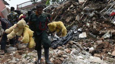 Un soldat sri-lankais marche, le 17 avril 2017, à travers des décombres après l'effondrement d'une décharge dans la banlieue de Colombo