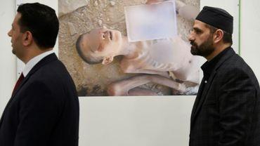 Des membres de l'organisation syrienne pour les victimes de la guerre (SOVW) regardent des photographies montrant la torture de détenus dans les prisons et les centres de détention du régime d'Assad, le 17 mars 2016 à Genève