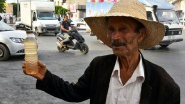 Un homme vend une bouteille de legmi, de la sève de dattier, dans une rue de Gabès, dans le sud de la Tunisie, le 18 juillet 2019.