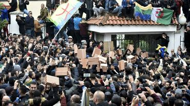 Des manifestants algériens brandissent les drapeaux algérien, amazigh (berbère) et soulèvent des briques, lors d'un rassemblement à Tizi Ouzou, une des principales villes de Kabylie (nord), le 8 décembre 2019