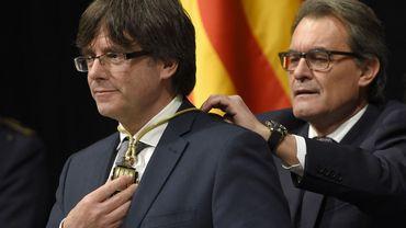 Artur Mas, ancien chef du gouvernement catalan, accroche une médaille autour du cou de Carles Puigdemont