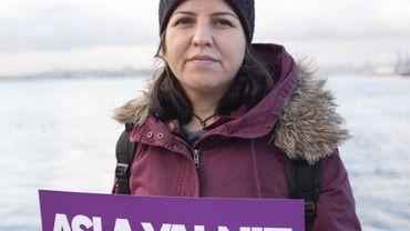 """Lors du rassemblement organisé par la plateforme contre les féminicides le 22 novembre 2020 à Istanbul, Münevver Kızıl tient une pancarte où il est inscrit """"Tu ne marcheras jamais seule""""."""