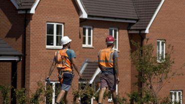 Des travailleurs de la construction marchent devant des constructions récentes à Bedford, au nord de Londres (Illustration)