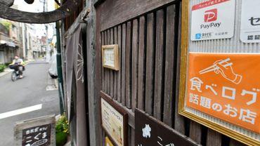 Une affiche vante le système de paiement électronique PayPay devant le restaurant Koguma à Tokyo, en juillet 2019