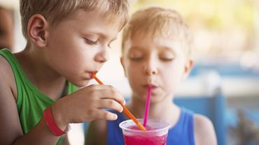 Little boys drinking soda with crushed ice on summer day