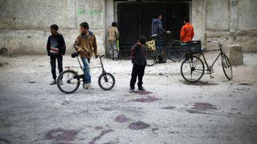 Des enfants sur le site d'un bombardement du régime qui a tué au moins quatre écoliers selon l'OSDH, le 31 octobre 2017 à Jisrine en Syrie