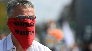 """Un homme anti-restrictions Covid-19 portant un masque """"la muselière de Merkel"""" manifeste le 12 septembre 2020 à Munich"""