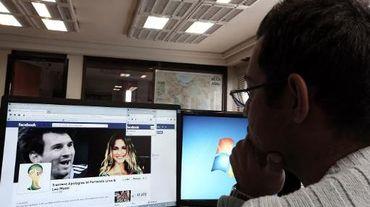 Un Iranien regarde une page Facebook contenant des photos de la star argentihne du football Lionel Messi et de la top-model brésilienne Fernanda Lima, le 9 décembre 2013 à Téhéran