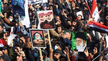 Des Irakiens brandissent à Bagdad des portraits du général iranien Qassem Soleimani et de son lieutenant irakien Abou Mehdi al-Mouhandis -tués dans une attaque américaine il y a un an-, le 3 janvier 2021