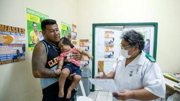 Une infirmière parle avec un père de famille et sa fille dans une clinique de Apia, le 4 décembre 2019