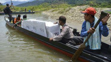 Transport d'urnes en pirogues, sur le fleuve Manggamat, à Aceh, en Indonésie, le 16 avril 2019