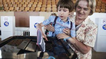 Un enfant glisse le bulletin de vote de sa grand-mère dans l'urne à Pristina le 8 juin 2014