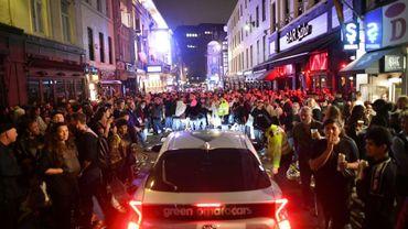 Une voiture essaye de traverser une rue pleine de fêtards dans le quartier de Soho à Londres, le soir du 4 juillet 2020