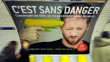 Des gens passent devant l'affiche d'une campagne contre les OGM menée par l'association France Nature Environnement, le 15 février 2011 dans le métro parisien