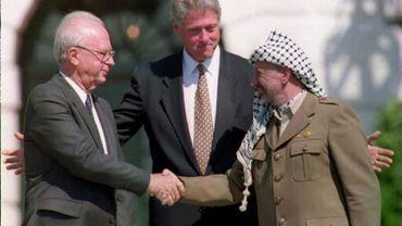 Le Premier ministre israélien Yitzhak Rabin et le leader de l'Organisation de libération de la Palestine (OLP) Yasser Arafat se serrent la main en présence du président américain Bill Clinton (c), le 13 septembre 1993 à Washington