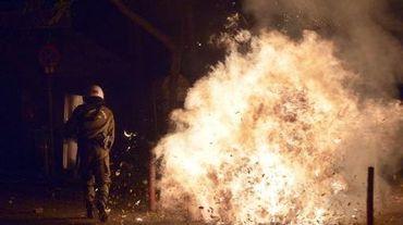 Un cocktail molotov explose près d'un policier grec lors de violences en marge d'une manifestations le 6 décembre 2014 à Athènes