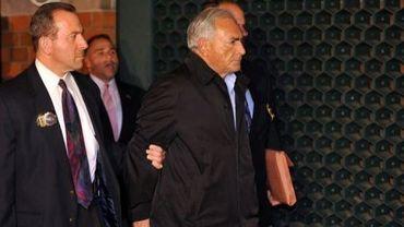 Dominique Strauss-Kahn (C) menotté, est escorté par des policiers à sa sortie du commissariat de Harlem le 16 mai 2011