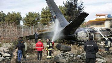 Des pompiers et des forces de sécurité interviennent sur le lieu du crash d'un avion militaire iranien près de Téhéran, le 14 janvier 2019