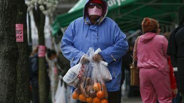 Une femme quitte le marché gratuit proposé à New York par l'association City Harvest, chargée de sacs de provisions, le 28 mars 2020