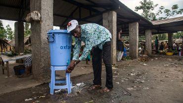 Un homme se lave les mains dans une citerne contenant du désinfectant, le 23 mai 2018 en République démocratique du Congo