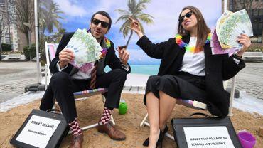 Des militants d'Oxfam mettent en scène un jeu de rue satirique imitant des personnes riches cachant leur argent dans un paradis fiscal, le 5 décembre 2017 près des institutions européennes à Bruxelles