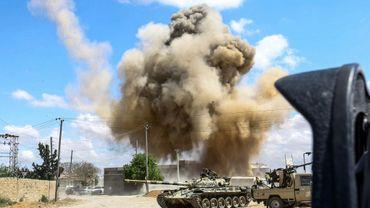 Photo prise le 12 avril 2019 montrant une colonne de fumée s'élever derrière des chars des forces loyales au Gouvernement d'union nationale (GNA) à Wadi Rabi, à quelque 30 km au sud de la capitale libyenne