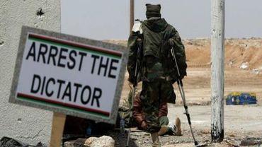 Un rebelle libyen le 21 avril 2011 à Ajdabiya où une pancarte réclame l'arrestation du dictateur
