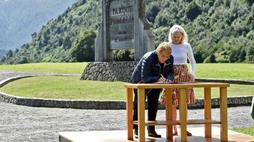 La présidente chilienne Michelle Bachelet (d) aux côtés de Kristine McDavitt, la veuvede Douglas Tompkins, millionnaire écologiste américain, signe un document faisant don de 407.625 hectares de terres au Chili, le 15 mars 2017 au parc Pumalin, dans le sud du pays