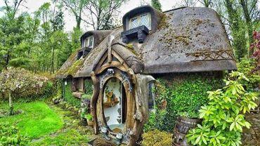 C'est une maison verte adossée à la colline.
