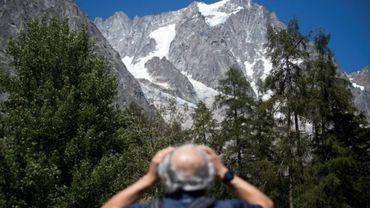 Un homme observe avec des jumelles le glacier de Planpincieux à Courmayeur, le 6 août 2020 au Val Ferret, en Italie.