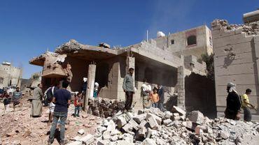 Des Yéménites passent devant un immeuble bombardé par la coalition militaire arabe, le 29 novembre dans la capitale Sanaa.