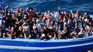 Migrants faisant signe à un navire de la flotte italienne, au large de Lampedusa, en janvier 2014
