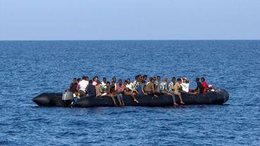 Au large des côtes libyennes, des migrants attendent d'être secourus par les garde-côtes italiens, le 6 août 2017