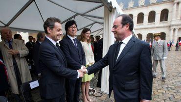 François Hollande et Nicolas Sarkozy se serrent la main lors d'une cérémonie aux Invalides, à Paris, le 25 septembre 2016.